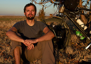 Christian Benke sitting in the grass in an apricot orchard in Turkey, part of his touring bicylce next to him